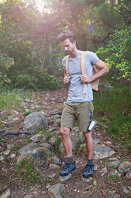 Buy stock photo Shot of a handsome man hiking in the forest