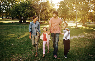 Buy stock photo Shot of a family walking together at the park