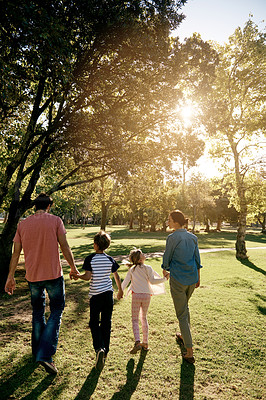 Buy stock photo Rearview shot of a family walking together at the park