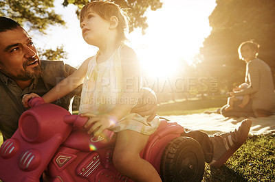 Buy stock photo Shot of a father and young daughter playing outside in a park
