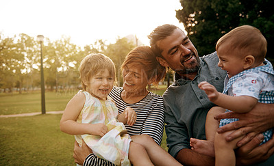 Buy stock photo Shot of a happy young family enjoying a day in the park