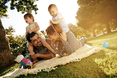 Buy stock photo Shot of a happy young family enjoying a sunny day in the park