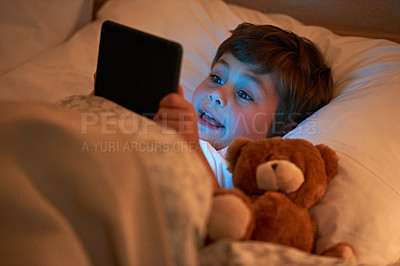 Buy stock photo Shot of a young boy using a digital tablet while lying in bed