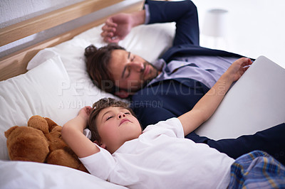 Buy stock photo Shot of a father and son sleeping on a bed while his father is still fully dressed and holding a laptop