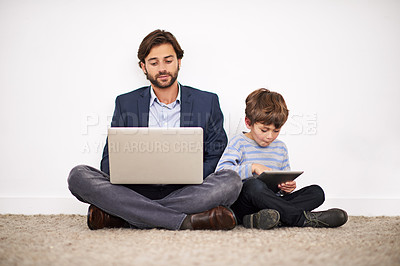Buy stock photo A father and son sitting on the floor against a wall with a laptop and digital tablet