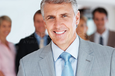 Buy stock photo Portrait of a happy mature businessman smiling with his staff in background