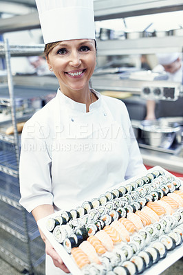 Buy stock photo Portrait of a chef holding a large platter of sushi in a restaurant kitchen