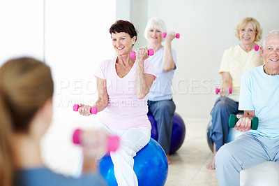 Buy stock photo A group of elderly people lifting weights together in a fitness class