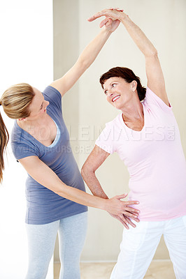 Buy stock photo A gym instructor helping and elderly woman get into the correct stretching position