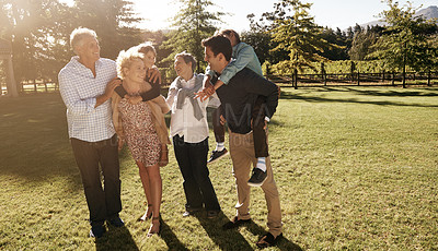 Buy stock photo Shot of a multi-generational family enjoying the outdoors together