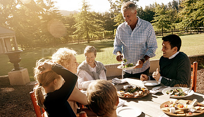 Buy stock photo Shot of a multi-generational family having lunch together outdoors