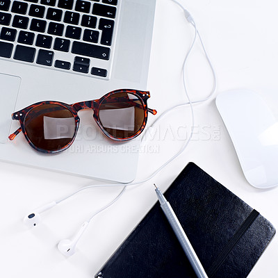 Buy stock photo Shot of a laptop, glasses, mouse and notebook on a table