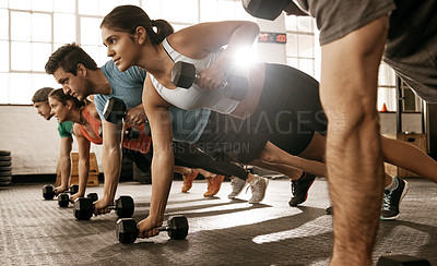 Buy stock photo Shot of a fitness group doing push-ups using dumbbells