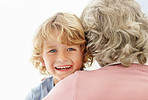 Cheerful kid hugging his grandmother against white background