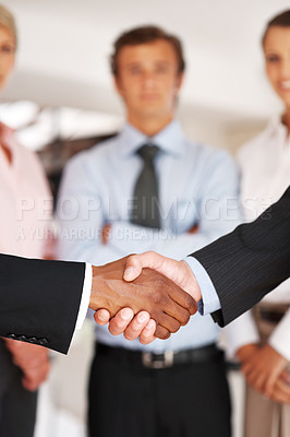 Buy stock photo Two businessman partners shaking hands in meeting with colleagues in background