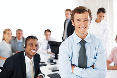 Buy stock photo Portrait of a smart young businessman smiling amd his colleagues working behind at office