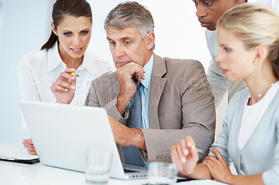 Buy stock photo Multi ethnic business executives using laptop at a meeting discussing work