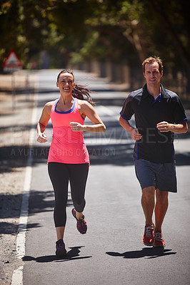 Buy stock photo Full length shot of a couple jogging on a road