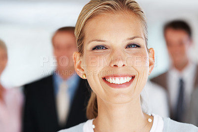 Buy stock photo Closeup portrait of a happy young businesswoman smiling and her colleagues standing behind