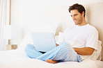 Smiling man working from home using a laptop