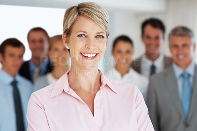 Buy stock photo Portrait of a smiling young businesswoman and her colleagues standing behind at office