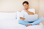 Happy handsome young man using a laptop in bed