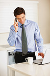 Young executive using cellphone and laptop while at the kitchen
