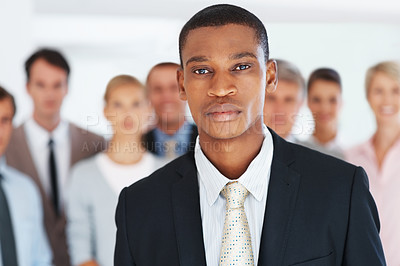 Buy stock photo Portrait of a confident young businessman looking and his colleagues standing behind at office