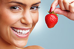 Cheerful young woman holding a fresh strawberry
