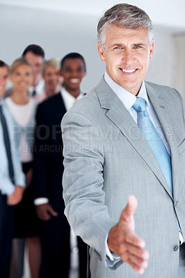 Buy stock photo Mature businessman extending his hand to shake with colleagues at the background