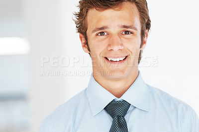 Buy stock photo Portrait of a successful young businessman smiling against bright background