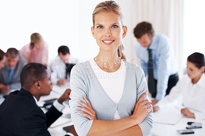 Buy stock photo Portrait of a happy young businesswoman smiling and her colleagues working in background