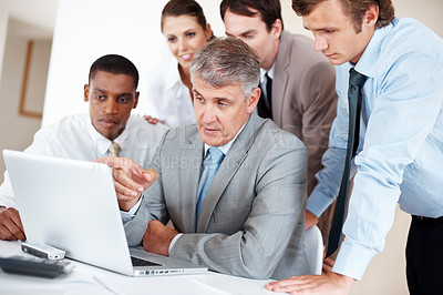 Buy stock photo Portrait of successful businessman discussing work with his colleagues
