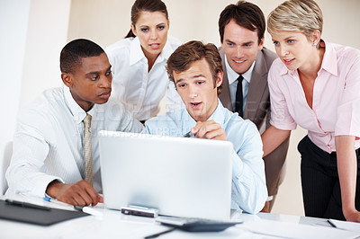 Buy stock photo Successful young businessman giving presentation to colleagues on laptop