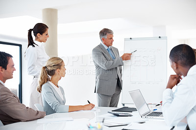 Buy stock photo Portrait of a senior manager giving presentation to his colleagues at the office