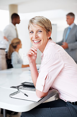 Buy stock photo Portrait of a pretty young executive smiling and her colleagues working on presentation  at the back