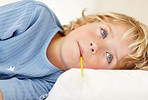 An ill boy lying on bed with thermometer in his mouth