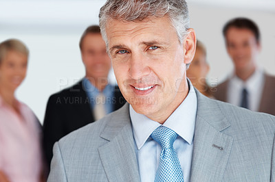 Buy stock photo Closeup portrait of a confident senior manager smiling and his colleagues standing behind at office