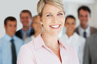 Buy stock photo Closeup portrait of a smiling young businesswoman with her group of associates standing behind