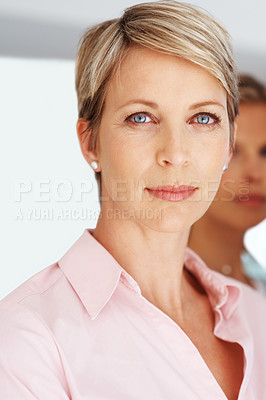Buy stock photo Portrait of a smart young businesswoman standing with colleague in background