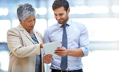 Buy stock photo Shot of two business colleagues discussing work while standing with a digital tablet