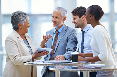 Buy stock photo A mature businesswoman with a tablet explaining something to her colleagues in a meeting