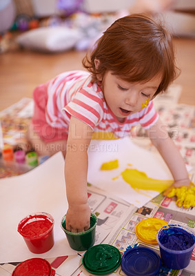 Buy stock photo Shot of an adorable little girl playing with paint at home