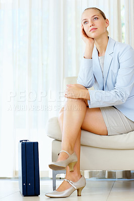 Buy stock photo Thoughtful business woman sitting at a waiting lounge with a briefcase