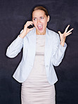 Angry business woman screaming over mobile phone against black