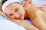 Relaxed young woman enjoying a back massage at a health spa