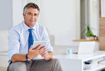 Buy stock photo Portrait of a mature businessman using a tablet while sitting on a sofa