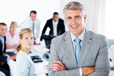Buy stock photo Successful senior manager smiling with his hands folded and his team working in background