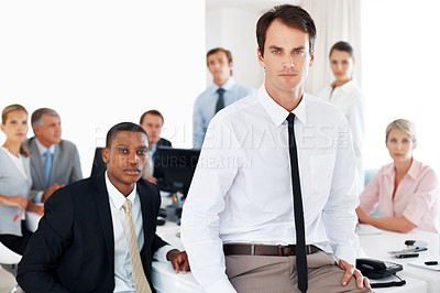 Buy stock photo Confident young businessman looking with an attitude with his colleagues behind at office