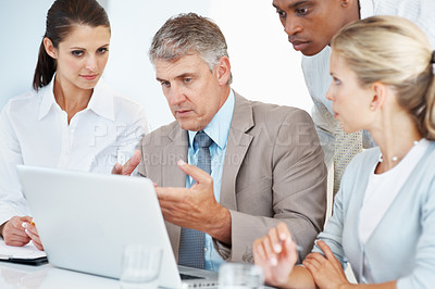 Buy stock photo Mature businessman working on laptop with colleagues at office - New business project